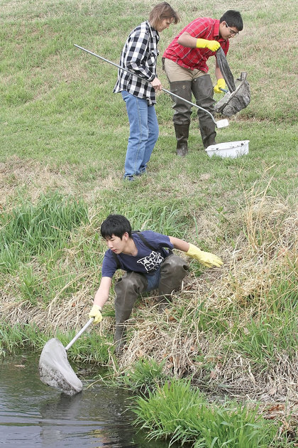 two students and a teacher cleaning up a river bed