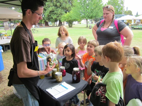 Outside - a man stands behind a small table showing children preserved food in jars. There is a teach standing behind the children
