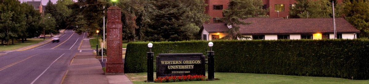 view of the campus entrance with WOU sign on the right and a street on the left